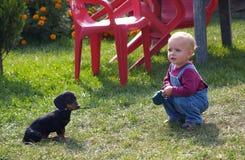 Muchacha que juega con el dachshund Imagen de archivo