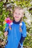 Muchacha que juega con el molino de viento en el fondo de un árbol floreciente foto de archivo libre de regalías