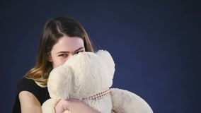 Muchacha que juega con el oso de peluche - aislado en a cámara lenta negro almacen de metraje de vídeo