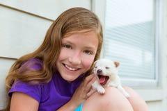 Muchacha que juega con el perro casero de la chihuahua del perrito Foto de archivo libre de regalías