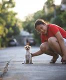 Muchacha que juega con el perro de perrito pomeranian en el pueblo casero Imagen de archivo libre de regalías