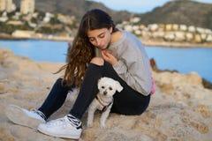 Muchacha que juega con el perro del maltichon en la playa Foto de archivo
