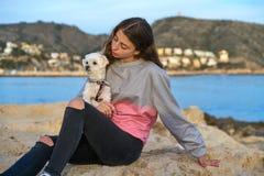 Muchacha que juega con el perro del maltichon en la playa Fotografía de archivo