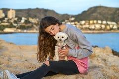 Muchacha que juega con el perro del maltichon en la playa Fotos de archivo