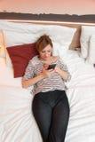 Muchacha que juega con el teléfono móvil imagenes de archivo