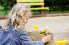 Muchacha que juega con la arena Fotografía de archivo libre de regalías