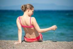 Muchacha que juega con la arena en la playa Imagen de archivo libre de regalías