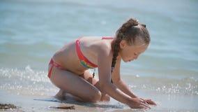 Muchacha que juega con la arena en la playa almacen de metraje de vídeo
