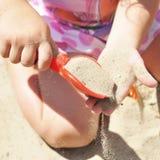 Muchacha que juega con la arena en una salvadera Fotos de archivo libres de regalías