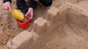 Muchacha que juega con la arena en la yarda metrajes