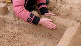 Muchacha que juega con la arena en la yarda Construcción del castillo de la arena almacen de video