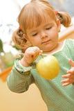 Muchacha que juega con la manzana Fotos de archivo