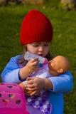 Muchacha que juega con la muñeca Fotografía de archivo