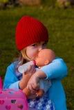 Muchacha que juega con la muñeca Imagen de archivo