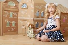 Muchacha que juega con la muñeca Foto de archivo libre de regalías
