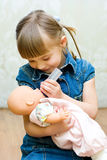 Muchacha que juega con la muñeca Imagen de archivo libre de regalías