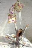 Muchacha que juega con las almohadas Fotografía de archivo