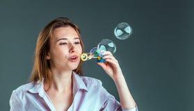 Muchacha que juega con las burbujas de jabón Fotografía de archivo