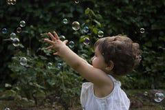 Muchacha que juega con las burbujas de jabón Foto de archivo libre de regalías