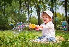 Muchacha que juega con las burbujas de jabón Imágenes de archivo libres de regalías