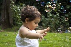 Muchacha que juega con las burbujas de jabón en el jardín Foto de archivo libre de regalías