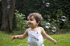 Muchacha que juega con las burbujas de jabón en el jardín Imagen de archivo libre de regalías
