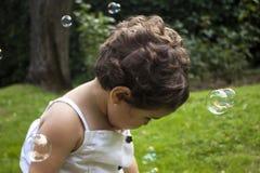 Muchacha que juega con las burbujas de jabón en el jardín Fotos de archivo