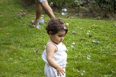 Muchacha que juega con las burbujas de jabón en el jardín Imagenes de archivo