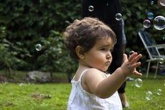 Muchacha que juega con las burbujas de jabón en el jardín Fotografía de archivo libre de regalías