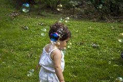 Muchacha que juega con las burbujas de jabón en el jardín Foto de archivo
