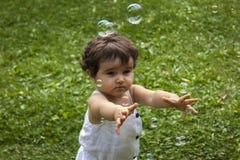 Muchacha que juega con las burbujas de jabón en el jardín Imágenes de archivo libres de regalías