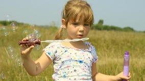 Muchacha que juega con las burbujas y agua de jabón almacen de metraje de vídeo