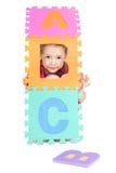 Muchacha que juega con las cartas del ABC del alfabeto Imagenes de archivo