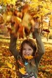 Muchacha que juega con las hojas de otoño para arriba en el aire Fotografía de archivo libre de regalías