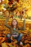 Muchacha que juega con las hojas de otoño para arriba en el aire Imagen de archivo