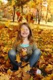 Muchacha que juega con las hojas de otoño para arriba en el aire Fotografía de archivo