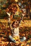 Muchacha que juega con las hojas de otoño para arriba en el aire Foto de archivo