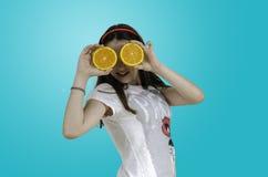 Muchacha que juega con las naranjas sobre fondo azul Imagen de archivo libre de regalías