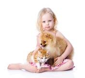 Muchacha que juega con los animales domésticos - perro y gato mirada de la cámara aislante fotografía de archivo libre de regalías