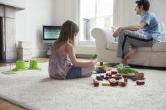 Muchacha que juega con los bloques mientras que padre Watching TV Imagen de archivo