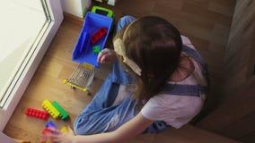 Muchacha que juega con los carros de la compra y los bloques del juguete almacen de metraje de vídeo