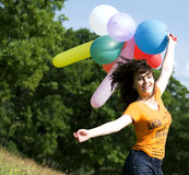Muchacha que juega con los globos del color Imagen de archivo libre de regalías