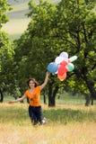 Muchacha que juega con los globos del color Imagen de archivo