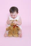 Muchacha que juega con los ojos ocultados del oso de peluche Fotos de archivo libres de regalías