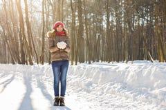 Muchacha que juega con nieve en parque Foto de archivo libre de regalías