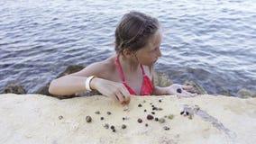 Muchacha que juega con Paguroidea en una playa almacen de metraje de vídeo