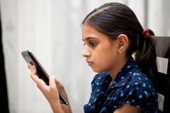 Muchacha que juega con su etiqueta Foto de archivo libre de regalías
