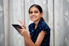 Muchacha que juega con su etiqueta Imagen de archivo