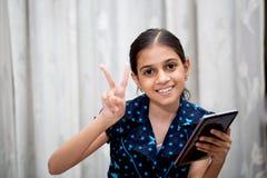 Muchacha que juega con su etiqueta Fotos de archivo libres de regalías