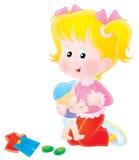 Muchacha que juega con su muñeca Fotos de archivo